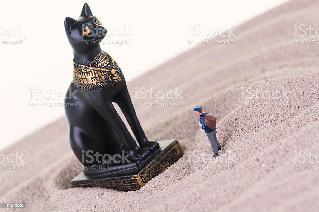 Miniature tourist with the Egyptian guardian Bastet statue stock photo
