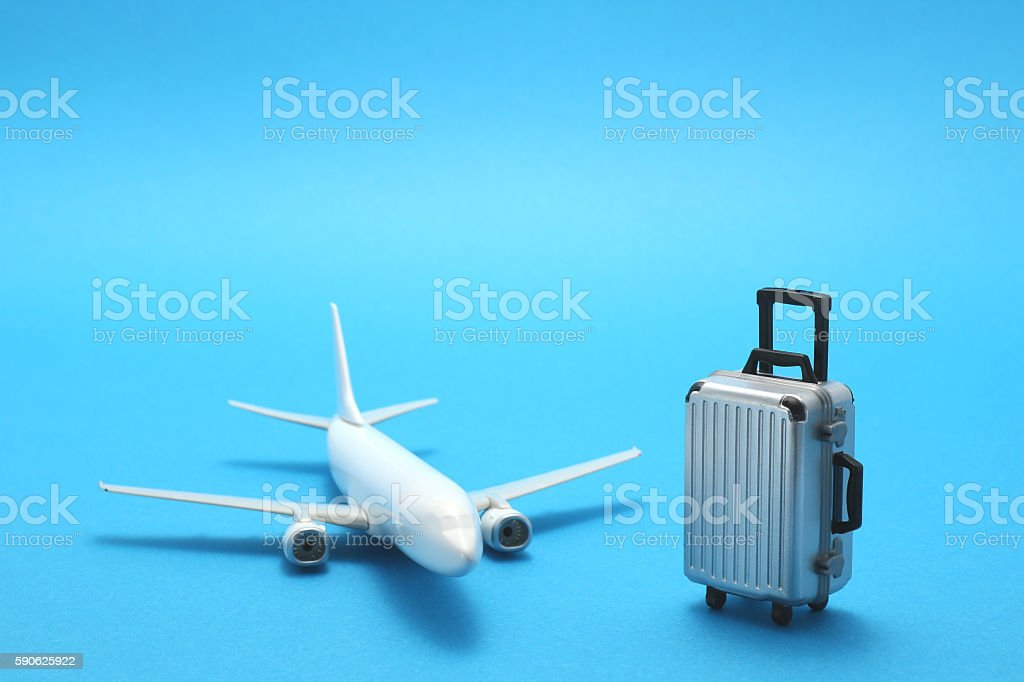 Miniature toy airplane and suitcase on blue background. stock photo
