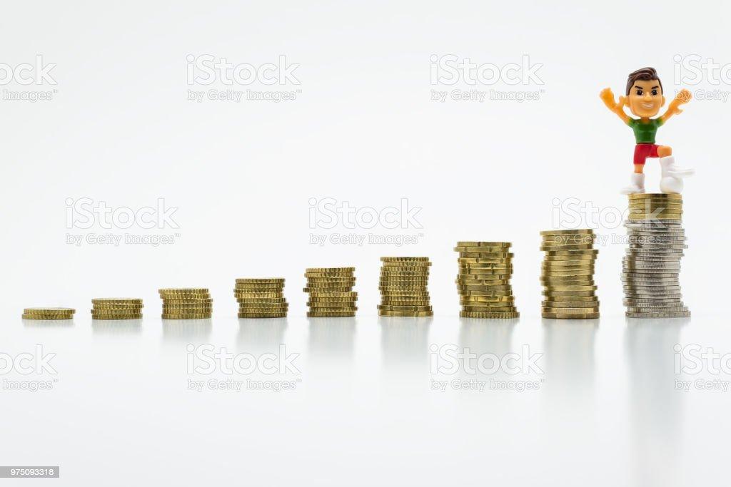 Hombre de juguete miniatura con un pie de fútbol en el crecimiento de monedas. El concepto de competición y Victoria. foto de stock libre de derechos