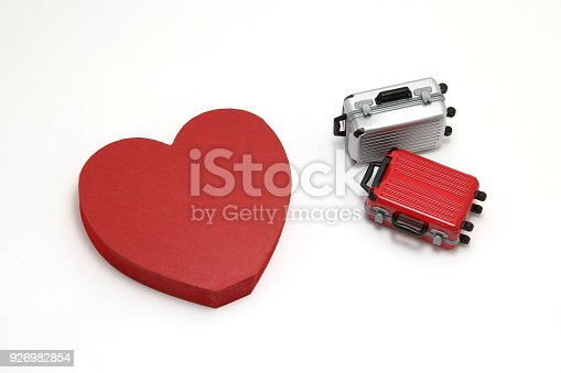 istock Miniature two suitcases and a red heart on white background. Concept of honeymoon. 926982854