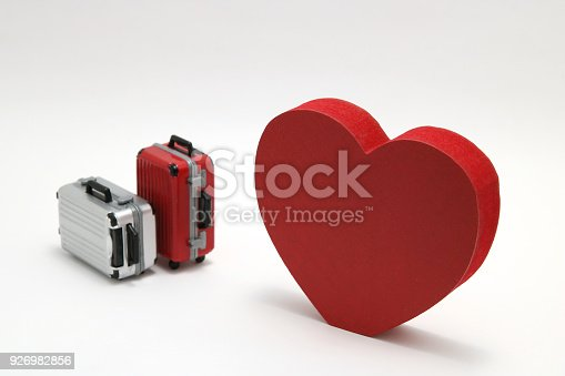 926982852 istock photo Miniature two suitcases and a red heart on white background. Concept of honeymoon. 926982856