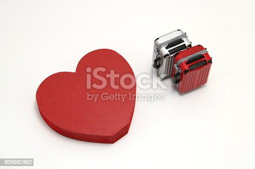 istock Miniature two suitcases and a red heart on white background. Concept of honeymoon. 926982862