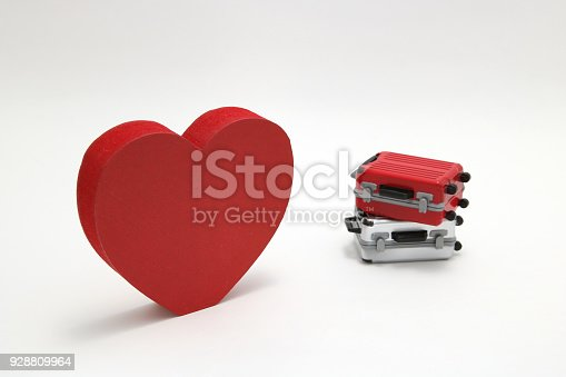 istock Miniature two suitcases and a red heart on white background. Concept of honeymoon. 928809964