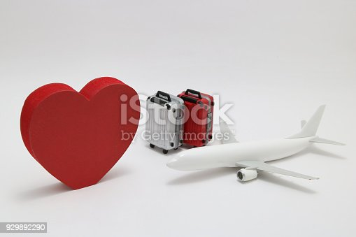 istock Miniature two suitcases, toy airplane, and a red heart on white background. Concept of honeymoon by airplane. 929892290