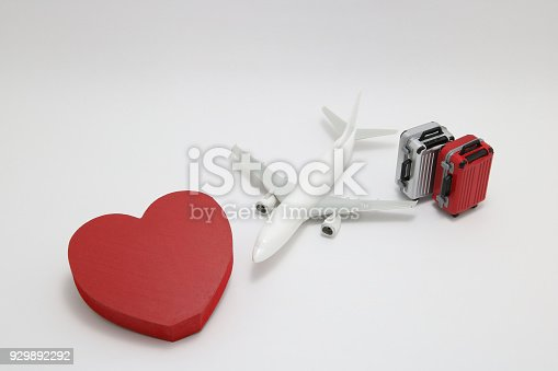 istock Miniature two suitcases, toy airplane, and a red heart on white background. Concept of honeymoon by airplane. 929892292