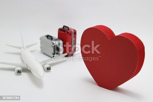 istock Miniature two suitcases, toy airplane, and a red heart on white background. Concept of honeymoon by airplane. 929892294