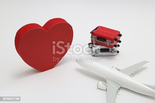 istock Miniature two suitcases, toy airplane, and a red heart on white background. Concept of honeymoon by airplane. 929892298