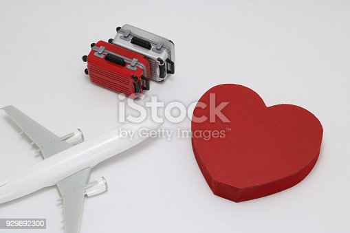istock Miniature two suitcases, toy airplane, and a red heart on white background. Concept of honeymoon by airplane. 929892300