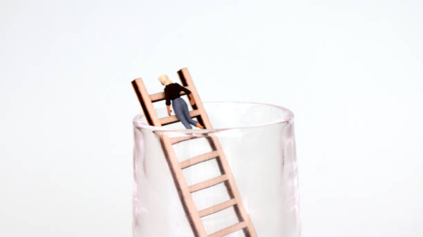 A miniature woman climbing up a ladder in a glass cup. The concept of the promotion limit for women. A miniature woman climbing up a ladder in a glass cup. The concept of the promotion limit for women. discriminatory stock pictures, royalty-free photos & images