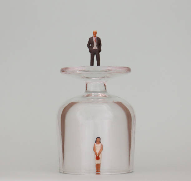A miniature woman in a glass cup and a miniature man on top of a glass cup. The concept of invisible barriers to women in promotion. A miniature woman in a glass cup and a miniature man on top of a glass cup. The concept of invisible barriers to women in promotion. discriminatory stock pictures, royalty-free photos & images