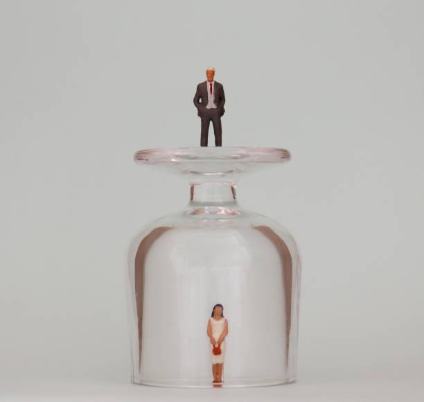 Eine Miniatur-Frau in eine Glasschale und ein Miniatur-Mann auf einer Glasschale. Das Konzept der unsichtbaren Barrieren für Frauen in Aktion. – Foto