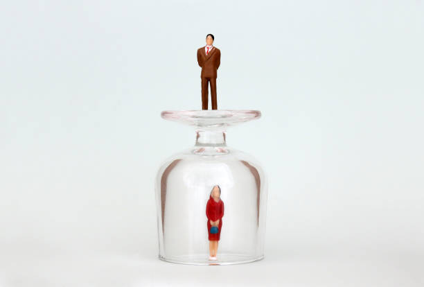 A miniature woman in a glass cup and a miniature man on top of a glass cup. The concept of the gender promotion gap. A miniature woman in a glass cup and a miniature man on top of a glass cup. The concept of the gender promotion gap. discriminatory stock pictures, royalty-free photos & images