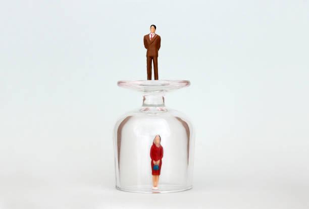 Eine Miniatur-Frau in eine Glasschale und ein Miniatur-Mann auf einer Glasschale. Das Konzept der Förderung zwischen den Geschlechtern. – Foto