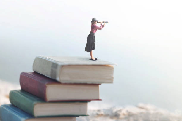 miniature woman looks at the infinity with the spyglass on a scale of books stock photo