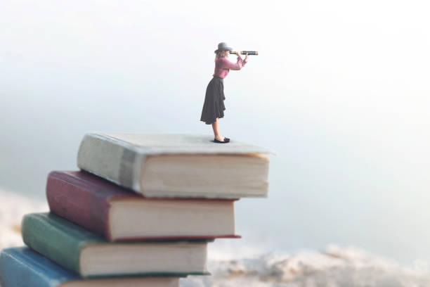 Miniatur-Frau schaut an die Unendlichkeit mit dem Fernglas auf einer Skala von Büchern – Foto