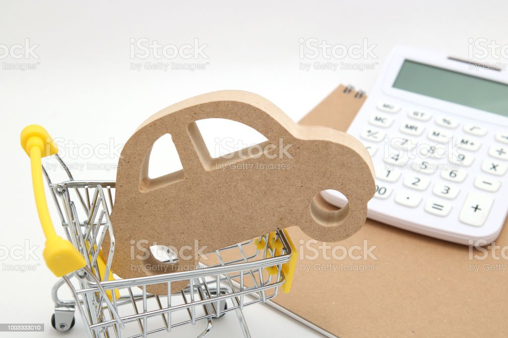 Miniature wooden car, shopping cart and  calculator on white background. Concept of buying new car. stock photo