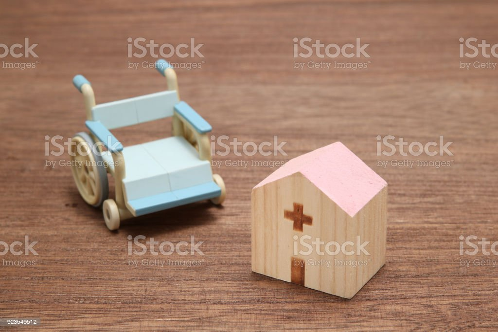 Miniature wooden hospital and blue wheelchair on wood. stock photo