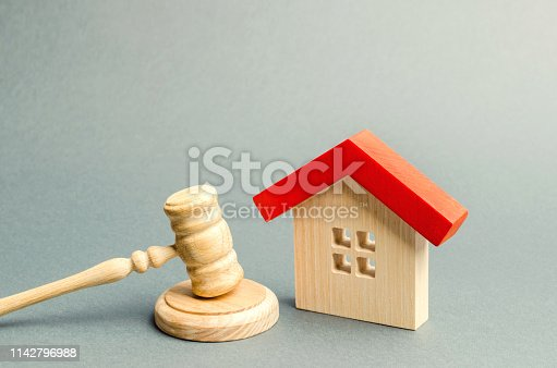 istock Miniature wooden house and judge's hammer. The concept of resolving property disputes. Property alienation. Confiscated housing. Nationalization. Services of a lawyer. Court. Gavel. Law 1142796988