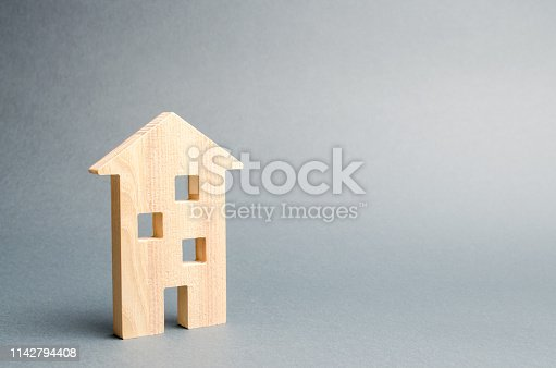 istock Miniature wooden house on a gray background. Real estate. Long-term rental apartments. Affordable housing for young families. Cheap property loans. Mortgage and loan. Construction of new buildings 1142794408