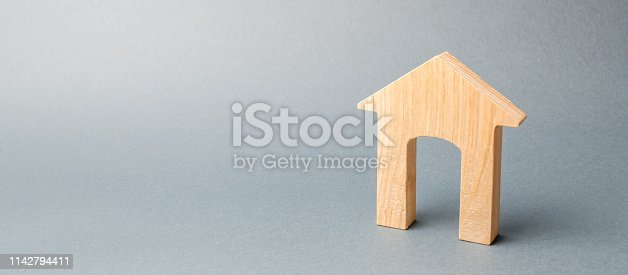 istock Miniature wooden house on a gray background. Real estate. Long-term rental apartments. Affordable housing for young families. Cheap property loans. Mortgage and loan. Construction of new buildings 1142794411