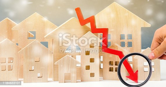 Miniature wooden houses and down arrow. The concept of low housing demand. Discounts for real estate in the winter. Mortgage, loan. Cheap cost. Christmas Snowflakes