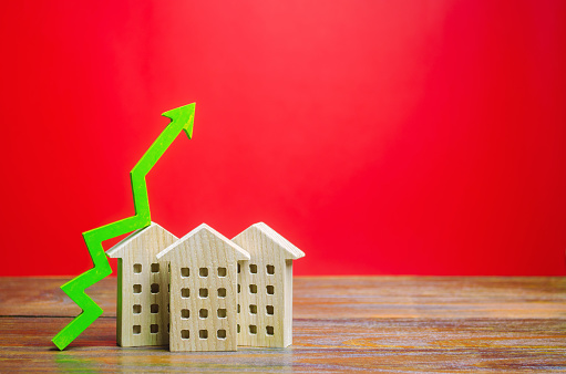 831745600 istock photo Miniature wooden houses and green arrow up. The concept of increasing the cost of housing. High demand for real estate. The growth of rent and mortgage rates. Sale of apartments. Population grows 1195432474