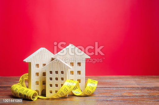 915688450 istock photo Miniature wooden houses and measuring tape. Home appraisal and property valuation concept. Housing construction, repair and maintenance. Real estate appraiser 1201441053