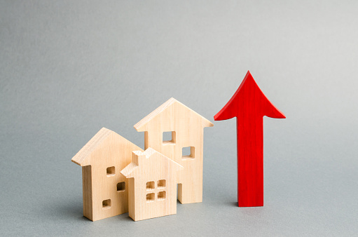istock Miniature wooden houses and red arrow up. The concept of increasing the cost of housing. High demand for real estate. The growth of rent and mortgage rates. Sale of apartments. Population grows 1142794040