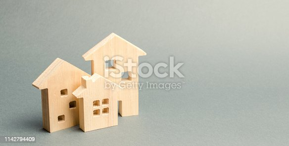 istock Miniature wooden houses on a gray background. Real estate. Long-term rental apartments. Affordable housing for young families. Cheap property loans. Mortgage and loan. Construction of new buildings 1142794409