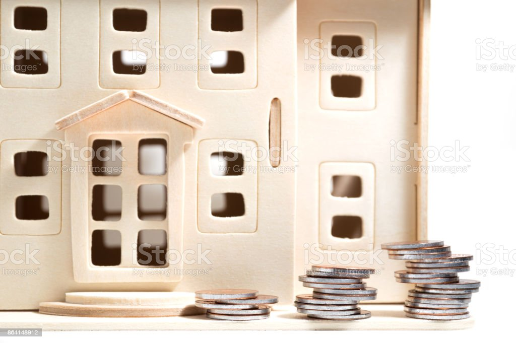 Miniature wooden toy house and korean coins isolated on white background royalty-free stock photo