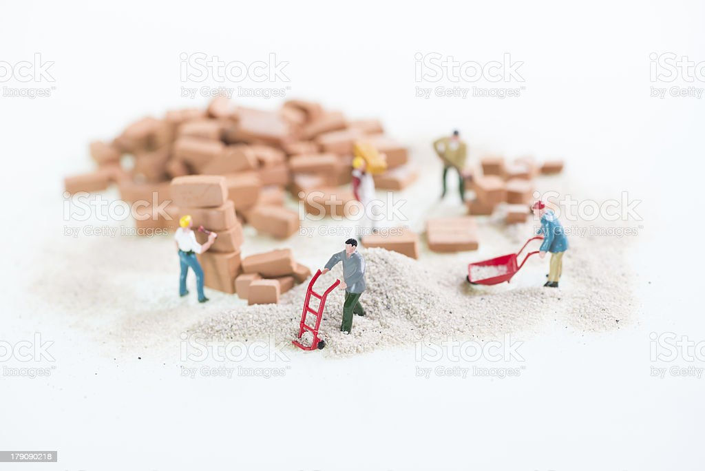 Miniature workmen doing construction work stock photo