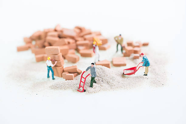 miniature workmen doing construction work - figurine stock photos and pictures