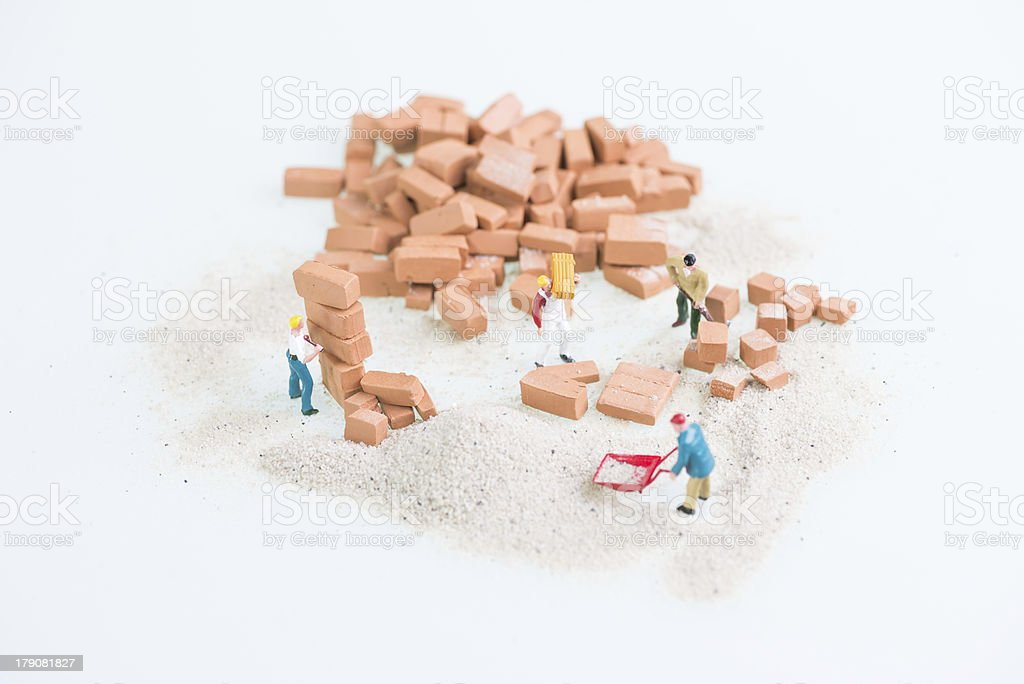 Miniature workmen working together in laying bricks royalty-free stock photo