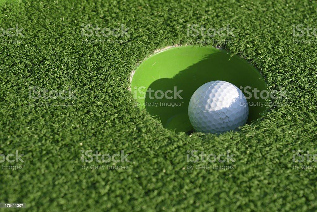 Minigolf ball in a hole closeup