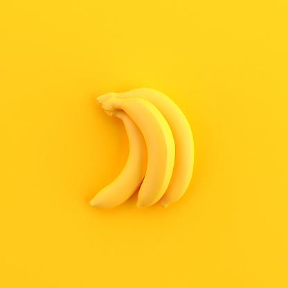 Minimal yellow painted bananas on yellow background