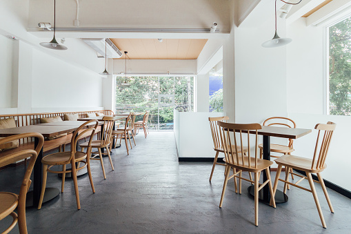 Minimal bread cafe decorating with white wall and wooden chairs. Warm, cozy and comfortable.