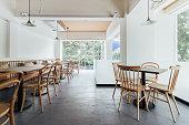 白い壁と木の椅子を飾る最小限パン カフェ。快適な居心地の良い、暖かい。