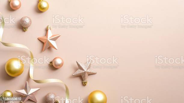 Minimal christmas background with gold balls pink stars ribbon on picture id1186453610?b=1&k=6&m=1186453610&s=612x612&h=lxsaeqh6ftakwfzup31xawou5ah1cuaugewsvf0rnru=