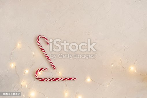 Minimal Christmas concept - Candy canes, garland lights, white background, top view, copy space.