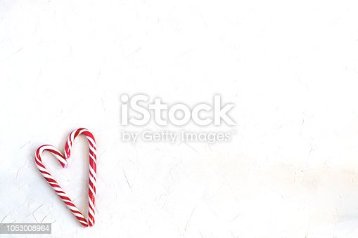 Minimal Christmas concept - Candy canes in shape of heart, white background, top view, copy space.