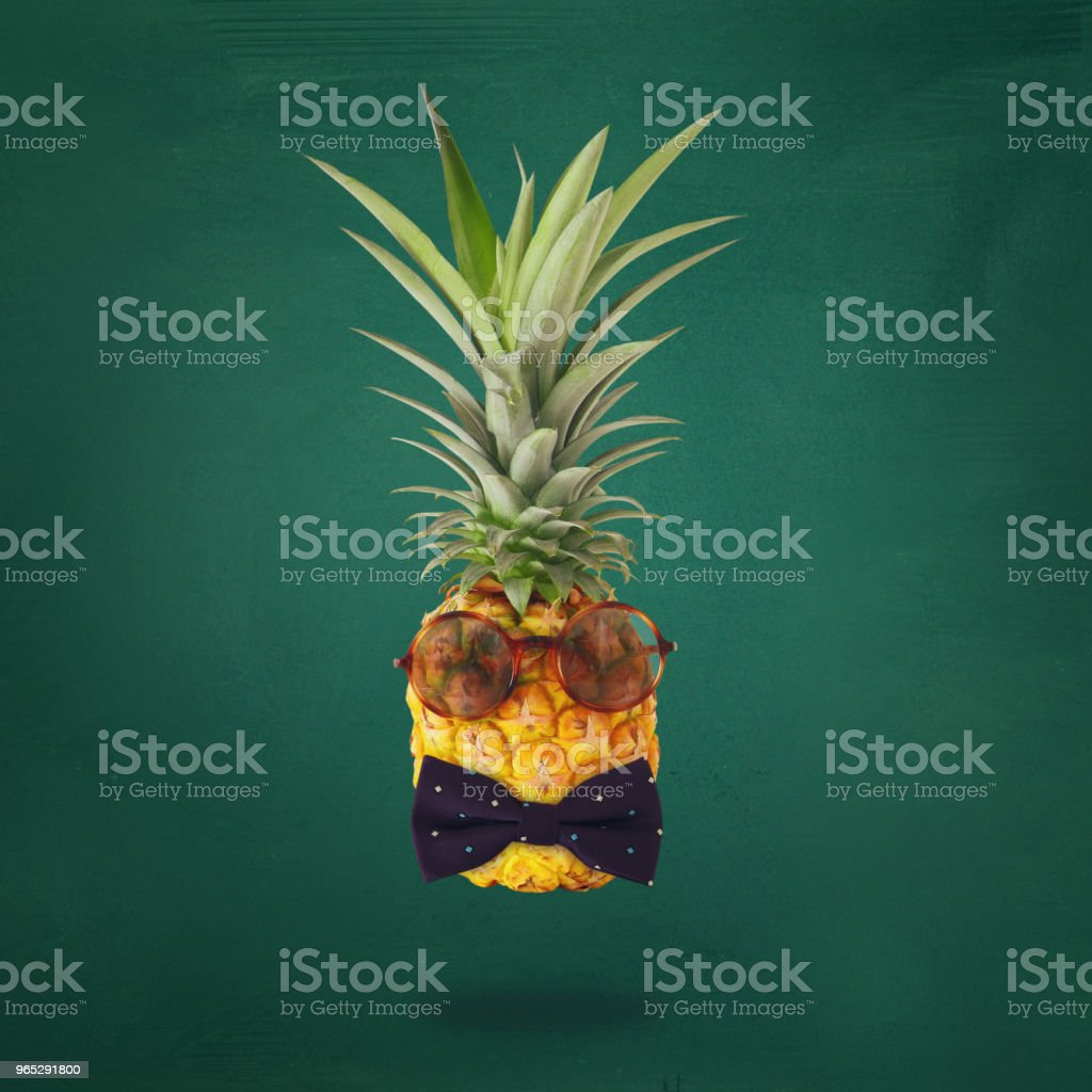 minimal concept. Cute and funny pineapple with sunglasses and bow tie over blackboard background. zbiór zdjęć royalty-free