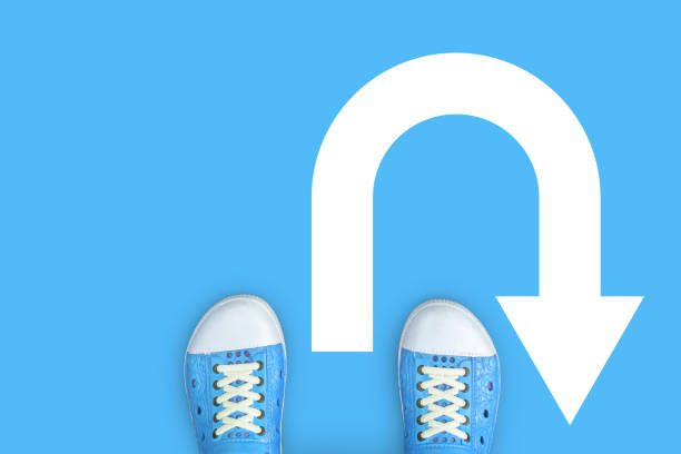 Minimal concept of u-turn, turn around and backward. Blue shoes standing on the floor and u turn sign Minimal concept of u-turn, turn around and backward. Blue shoes standing on the floor and u turn sign. bending over backwards stock pictures, royalty-free photos & images