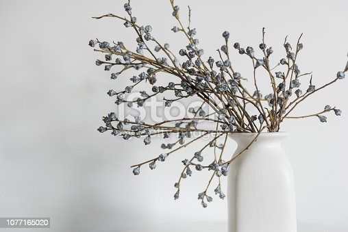 istock Minimal elegant composition with dried flowers on table. Vase of dried flowers with white wall background. 1077165020