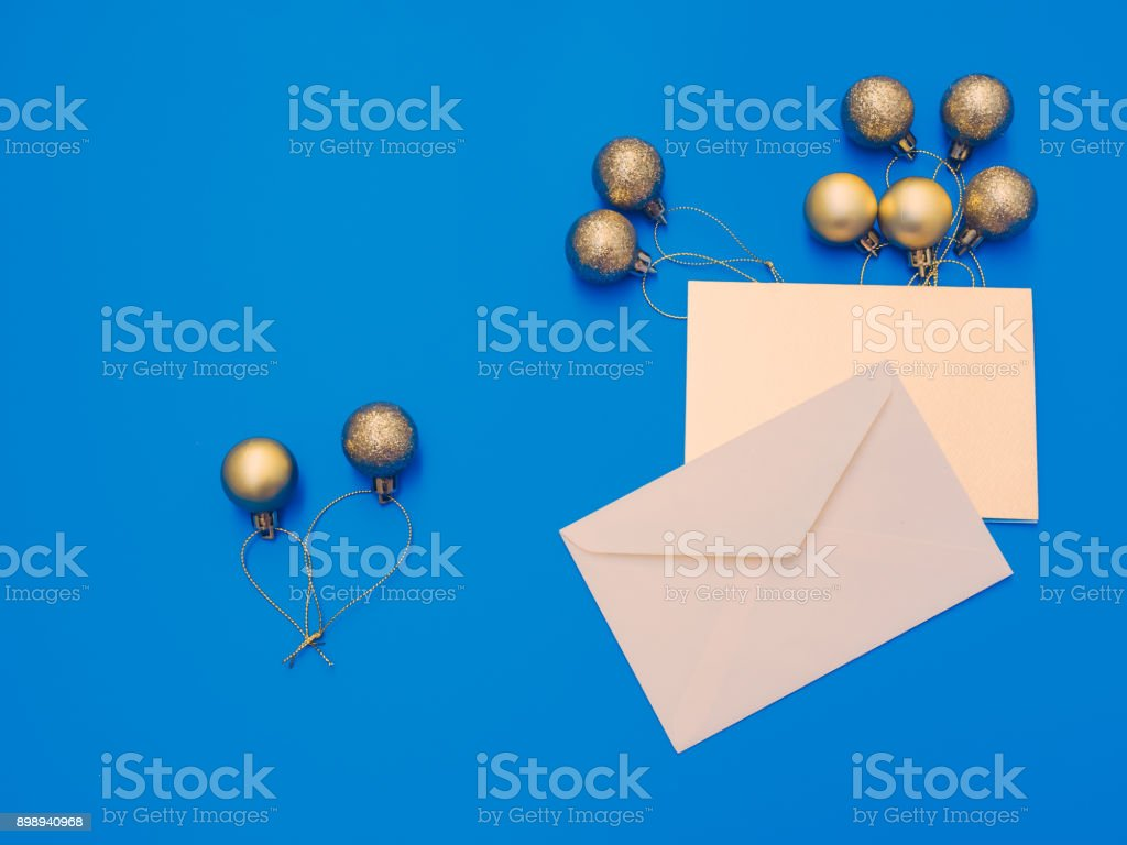 minimal flat lay by balloon flew away concept for christmas and new year event with greeting card and group of shiny gold ball or balloon arrange on table with isolated blue background stock photo
