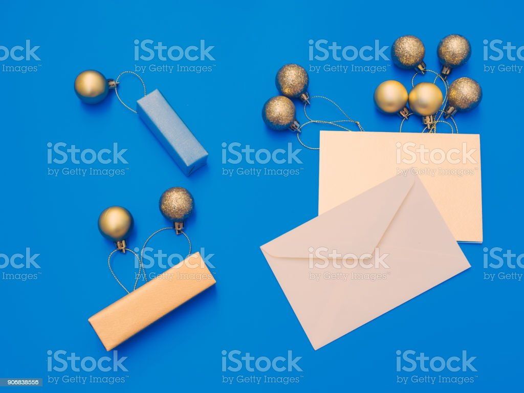 minimal flat lay by balloon flew away concept for christmas and new year event with greeting card , small gift box and group of shiny gold ball or balloon arrange on table with isolated blue background stock photo