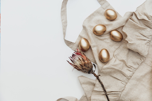 Minimal Flat lay Gold Easter eggs with linen apron and protea flower on white background. Top view, Still Life Happy Easter holiday concept