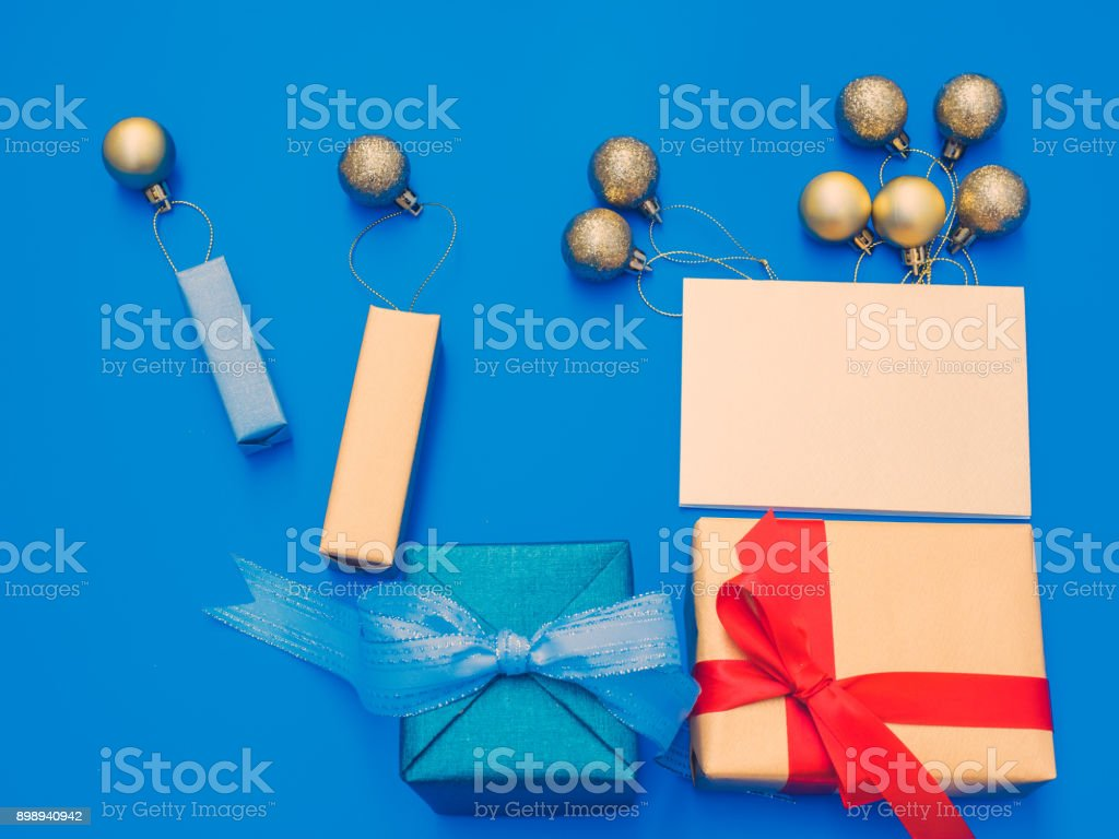 minimal flat lay style by balloon flew away concept for christmas and new year event with present box , greeting card and group of shiny gold ball or balloon arrange on table with isolated blue background stock photo