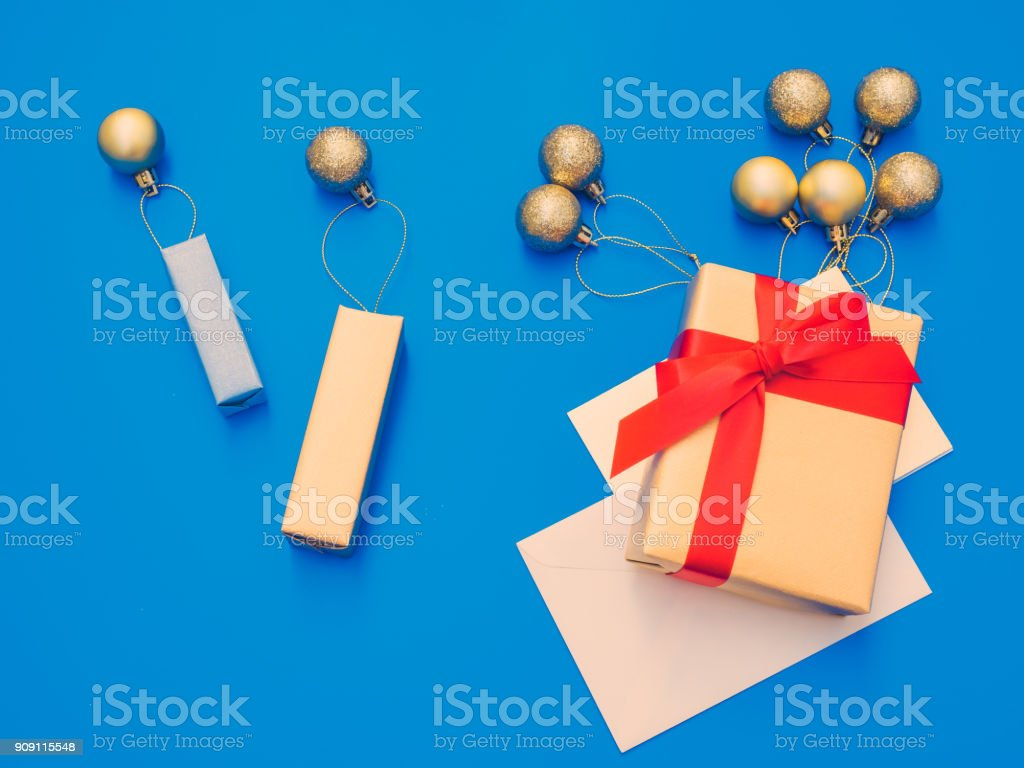 minimal flat lay style by balloon flew away concept for christmas and new year event with small present and group of shiny gold ball or balloon arrange on table with isolated blue background stock photo