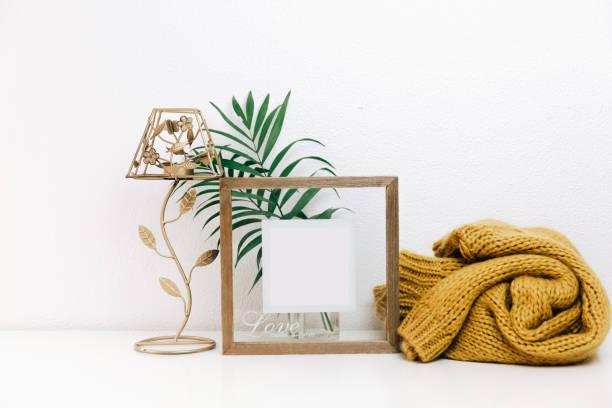 minimale mock-up holzrahmen mit grünen tropischen blättern und trendige warme pullover. nordische dekorationen, skandinavischen stil eingerichtet - sideboard skandinavisch stock-fotos und bilder