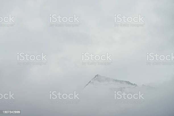 Photo of Minimal mountain landscape with high pointy rock in clouds. Minimalist mountain scenery with sharp snowy mountain peak over clouds. Snow-white pointed pinnacle above white clouds. Big top in dense fog